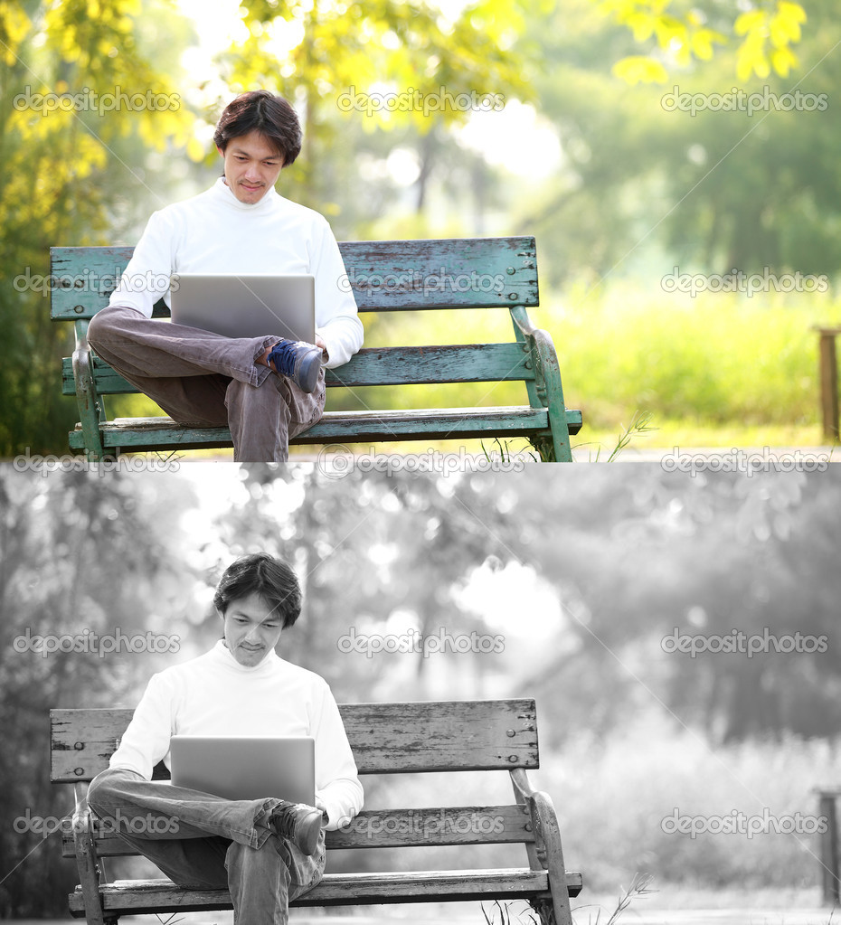 A young handsome man using laptop sitting on a bench in a park.