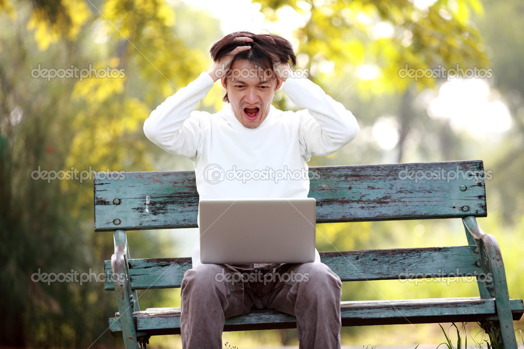 A young handsome man asian using laptop sitting on a bench in a