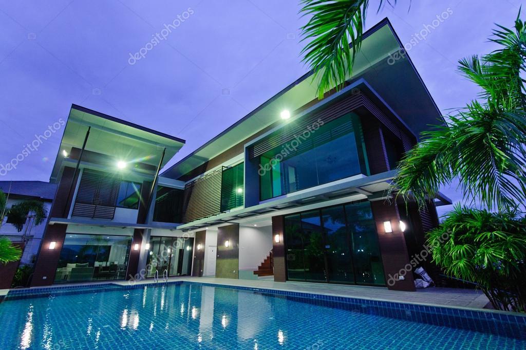 Casa moderna con piscina de noche foto de stock for Piani di casa con pool house