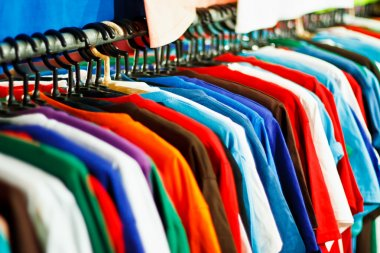 Colors of rainbow. Variety of casual shirts on hangers