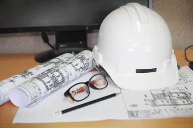 File of safety helmet and architect plant on wood table