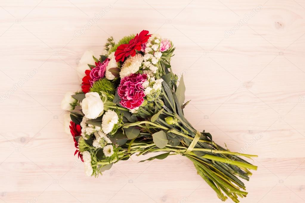 Bouquet of white, pink and red flowers on a wooden surface