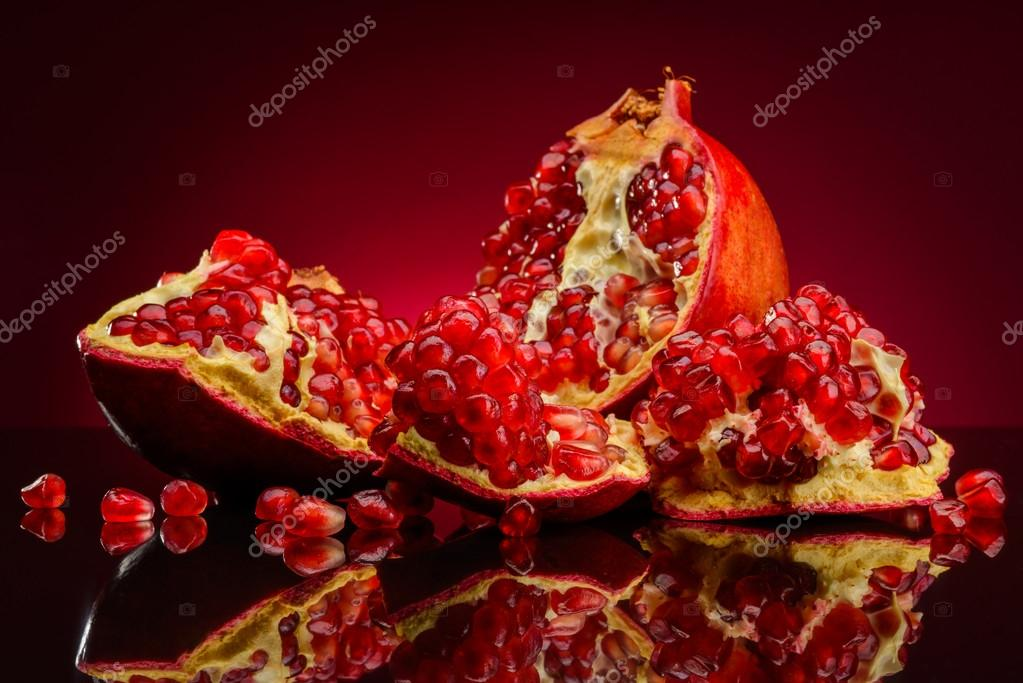 Pomegranate fruits on a red background