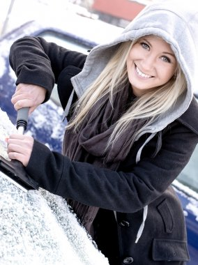 Young woman scraping ice from car