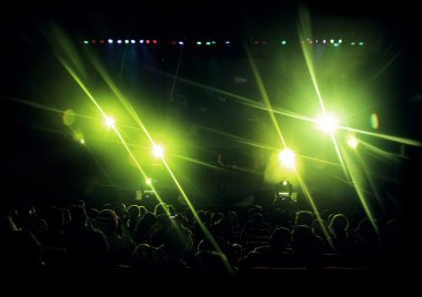 Stage with green light flares and audiences.