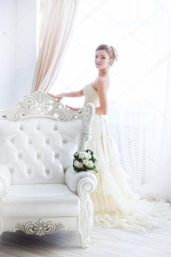 Young bride near curtains.
