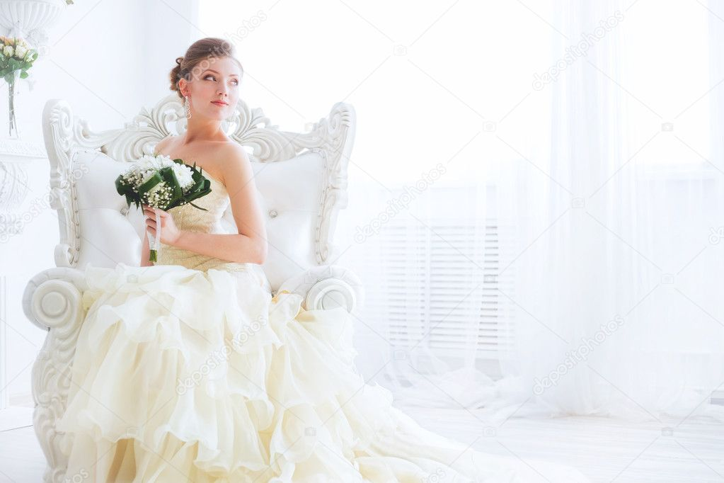 Young bride is sitting in an armchair with flowers.