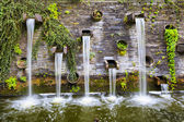 Fotografie skalní stěna s malými vodopády v parku planten un blomen