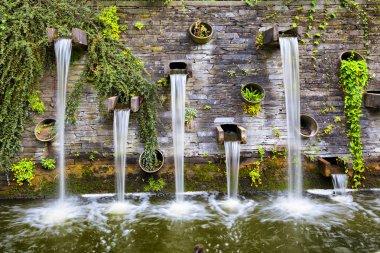 Rocky wall with small waterfalls in Planten un Blomen park