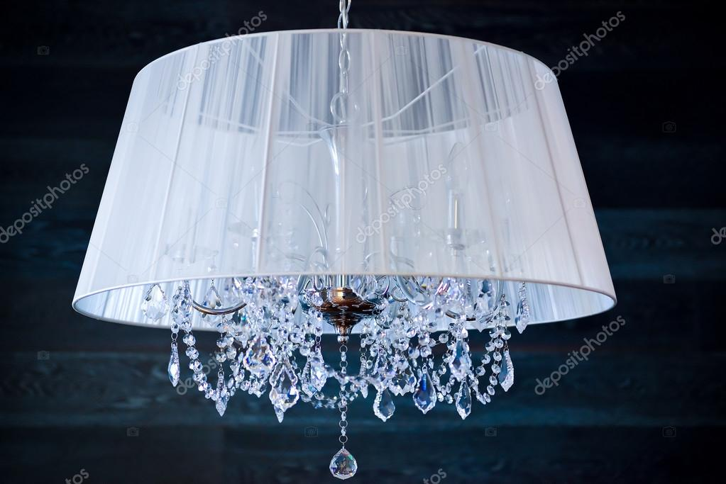A crystal chandelier with a white shade