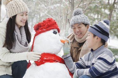 Family making snowman in winter