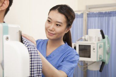 Doctor Examining Patient With X-ray Machine