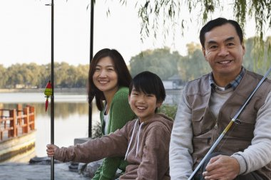 Family portrait with fishing gear at a lake