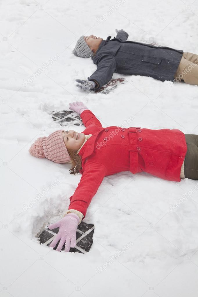 Couple laying in snow making snow angels