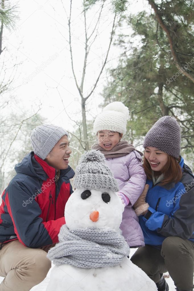 Family making snowman in winter