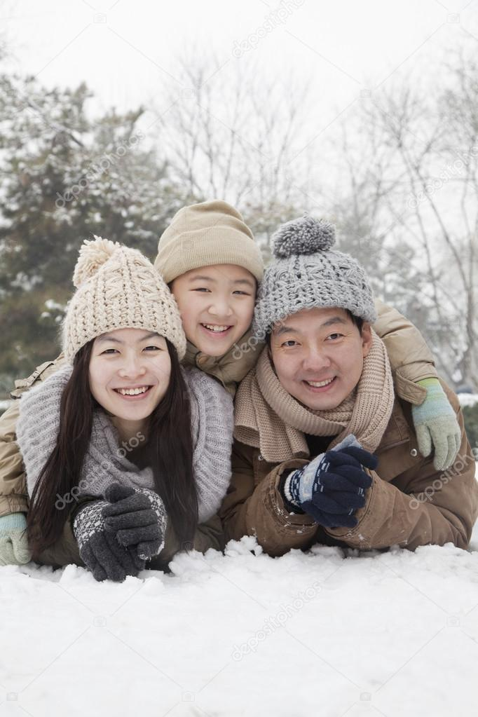 Family laying in snow