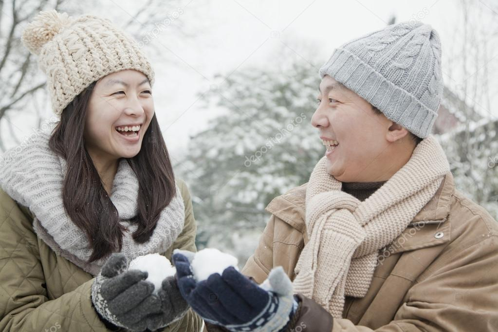Couple Holding snow balls in park