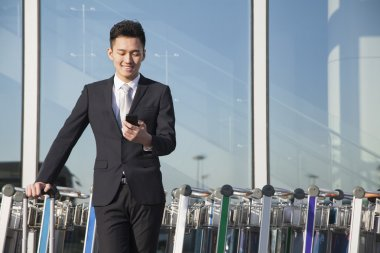 Traveler looking at cellphone next to row of luggage carts