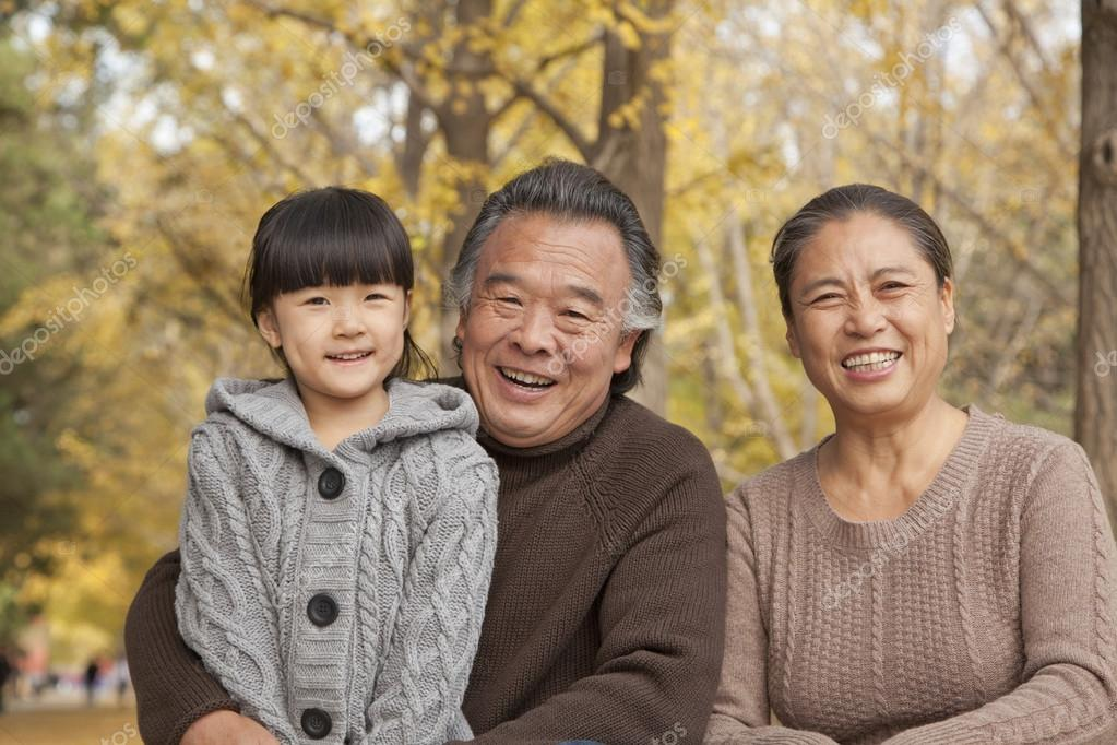 Grandparents and granddaughter in park