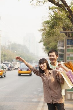 Couple hailing a taxicab