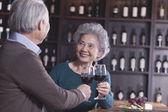 Seniorenpaar stößt an und trinkt Wein