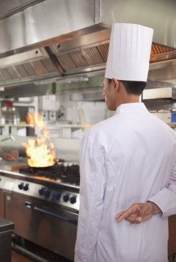 Chef with Fingers Crossed as a Pan Catches Fire