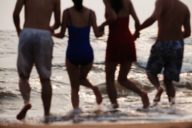 Friends running into the water on a sandy beach