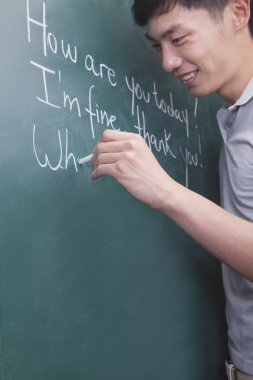 Man writing English sentences on the blackboard
