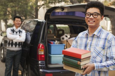 Boy unpacking car for college