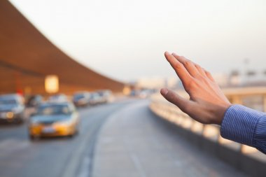 Hand of traveler hailing a taxi