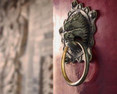 Ornate gold door knocker on red door