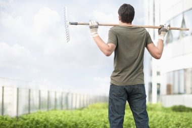 Man holding a rake on his shoulders