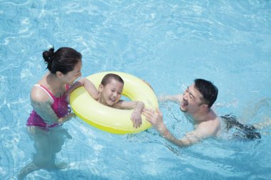 Family playing in the pool with their son