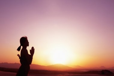 Woman with hands together in prayer pose in the desert