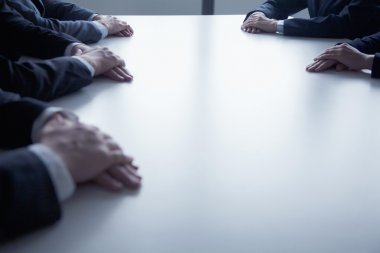 Folded hands of business people at the table