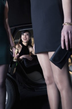 Women arriving at a red carpet event in a car
