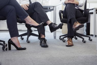 Business people with legs crossed sitting on chairs