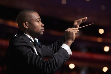 Conductor with baton raised at a performance