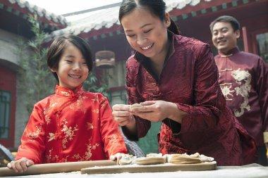 Mother and daughter making dumplings
