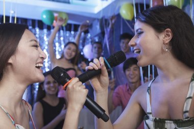 Friends and singing together at karaoke