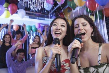 Friends singing together at karaoke