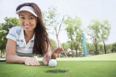 Smiling young woman lying down in a golf course
