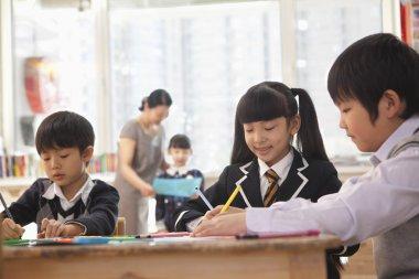 School children drawing during art class