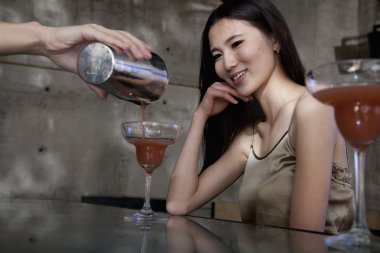 Bartender serving a cocktail to a young woman