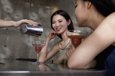 Women having cocktails, sitting at the bar counter