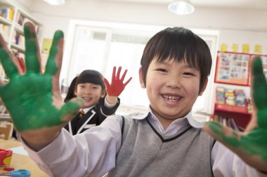 School children showing their hands covered in paint