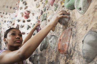 Woman climbing up in an indoor climbing gym