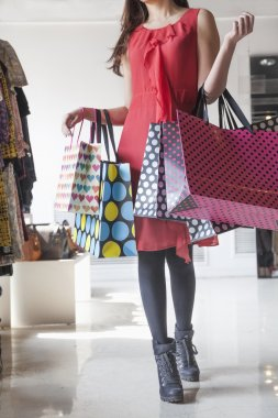 Woman with shopping bags at fashion store