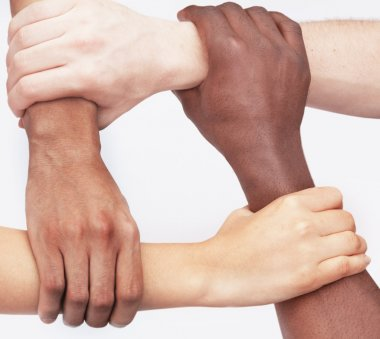 Four people holding each others wrists in a circle