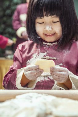 Little girl making dumplings in traditional clothing